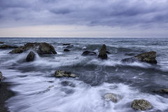 Waves on rocky shores Stock Photos
