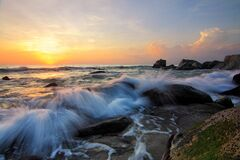 Waves on rocky shores at sunrise