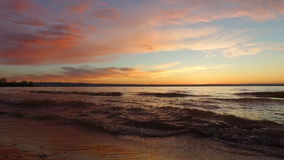 Waves roll on the sandy shore. Evening, the sun has already gone beyond the horizon. In the distance, another bank of a large lake. Is visible. Beautiful red stock footage