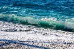 The waves rolled onto the beach of pebbles.  Stock Photography