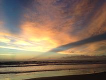 Waves Rolling on Atlantic Ocean Beach during Dawn with Crepuscular Rays. Stock Image