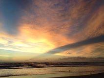 Waves Rolling on Atlantic Ocean Beach during Dawn with Crepuscular Rays. Royalty Free Stock Photo