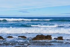 Waves rolling to the rocks, Foamy Splashes, Victoria, Australia. Barwon Heads, Barwon Bluff, Ocean waves rolling to the shore, rocks at the shore, blue natural Stock Photo