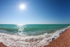 Waves rolling to shore under a sky with the sun Stock Photography