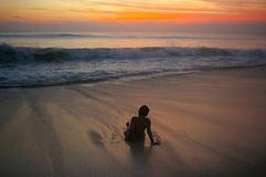 Waves rolling towards a boy Stock Images
