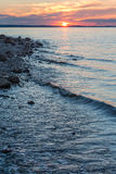 Waves run on the rocky shore of the river. Summer sunset Stock Images