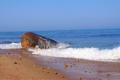 Waves running over Boulder. Boulder in surf Royalty Free Stock Photos