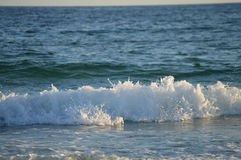 Waves Rush In. Waves whitecap as they rush into the beach stock photography