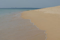 Waves rushing to the sand, the ocean shore near Porto Covo, Portugal. Royalty Free Stock Photo
