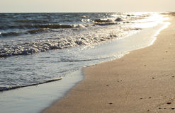 Waves and sand of beach caribbean sea on the sunset light. Royalty Free Stock Photography