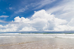 Waves sand beach and clouds sunny day Royalty Free Stock Images