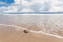 Waves sand beach and clouds sunny day Royalty Free Stock Photos