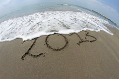 Waves of the sea on the beach that erase the year 2013 Stock Photography
