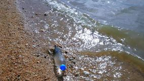 Waves of the sea beat on a water bottle in shore. stock footage