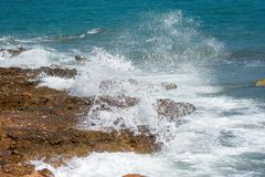 Waves of the sea foaming, breaking against the rocky shore Stock Photos