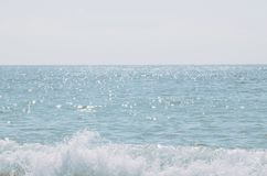 The waves of the sea. The glare of the sun in the water. The blue background of the sea royalty free stock image