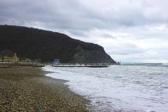 Sea, mountain, overcast sky and sandy coast stock images