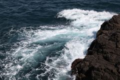 Waves in the sea among the rocks. Ripples of waves in the sea Stock Photography