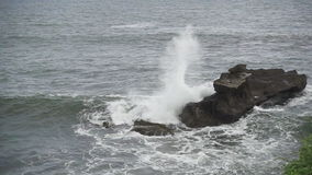 Waves of the sea roll on the stony coast, slow motion shot, stock footage