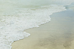 Waves on sea sand at low tide Stock Images