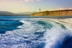 Waves at sea after ship, a lighthouse on a high bank Stock Image