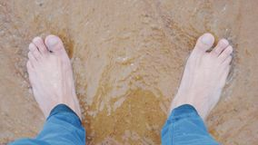 Waves of the sea surf washed men's feet in jeans on white sand. Top view stock video