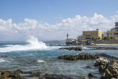 Waves at the seacoast with old lighthouse in Tyre, Sour, Lebanon Royalty Free Stock Photo