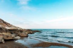 Waves on seashore. Seashore, rocks and surf on beach Stock Image
