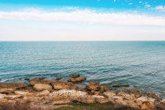 Waves on seashore. Seashore, rocks and surf on beach Royalty Free Stock Photo