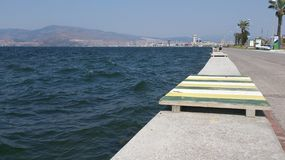 Waves in seaside in Konak, Izmir. Sea landscape with mountain and buildings on background and green white yellow colored wooden sit on front Royalty Free Stock Photo