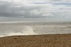 Waves on shingle beach at  Hastings Stock Photo
