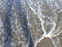 Waves on the shore of a beach. Foamy ocean water on the beach Royalty Free Stock Photos