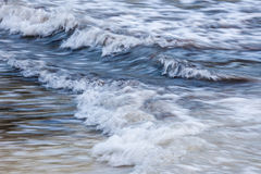 Waves at shore. Blue foamy ocean waves breaking in shallow water, in-camera motion blur Stock Photos