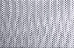 Waves on a silver background, wavy sheet metal. Stock Photography