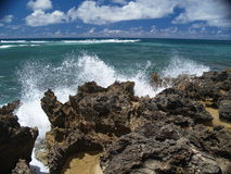 Waves and Skies. Waves break along the volcanic rock on the North Shore of Oahu Royalty Free Stock Images
