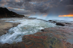 Waves smash against the rocks at Coledale Stock Images