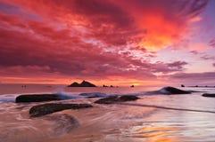 Waves som kraschar med den ljusa färgrika skyen Arkivbilder