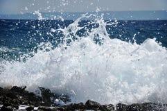 Waves som krossar på en stenig strand Arkivfoton