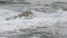 Waves spashing on submerged rock stock footage