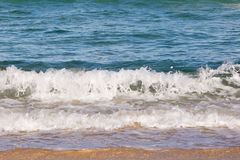 Waves spashing on to sand stock photography