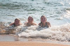 Waves Splash Girls Laying on the Sand Stock Images