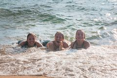 Waves Splash Girls Laying on the Sand Stock Photography