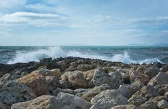 Waves splash onto rocks. On a windy day in December in Mallorca, Balearic islands, Spain Stock Images