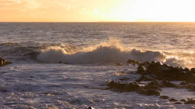 Waves splashing against morning sun stock footage