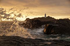 Lighthouse at sunrise sunset with rough seas waves stock images