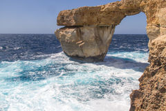 Waves splashing againt a large rock. The Azure Window on Gozo Malta on a sunny and windy day. Waves are splashing against the rocks Royalty Free Stock Image