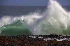 Waves splashing on basalt rocks at Ocean beach Bunbury  Western Australia. The waves splashing on ancient  dark  basalt rocks at Ocean beach Bunbury  Western Stock Image