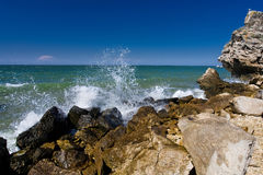 The waves splashing on the beach with rocks. And blue sky Royalty Free Stock Photography