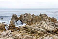 Waves splashing on huge rocks, along a rocky beach Royalty Free Stock Photography