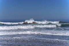 Waves splashing on huge rocks, off shore, Stock Photo